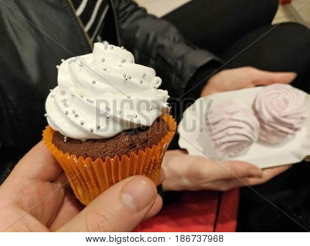 Cream cakes close-up. In the man's hand a chocolate cake covered with white cream and silver balls. In the background, women's hands with two marshmallows