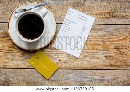 credit card for paying, cup of coffee and check on cafe wooden desk background top view mock up