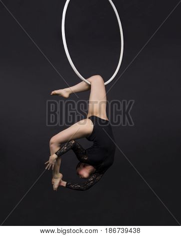 A young girl performs the acrobatic elements in the air ring. Studio shooting performances on a black background.