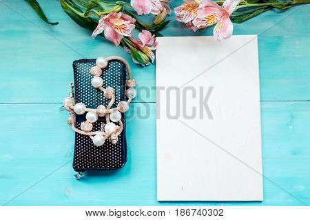 Spring background of bonded wooden boards with a Board of the label layout on a blue wooden background with flowers blackboard purse and beads decoration