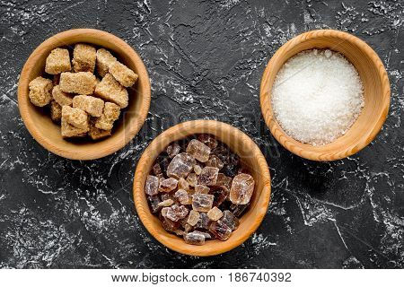 cooking sweets set with sugar in bowls on kitchen dark table background top view