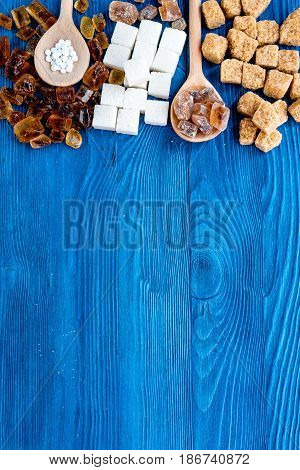 lumps of sugar with spoons sweet set on blue kitchen table background top view mockup