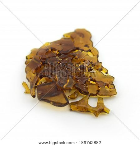 Cannabis shatter concentrate isolated on white backdrop
