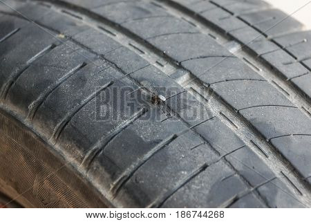 Closeup of care tire puncture due to nail
