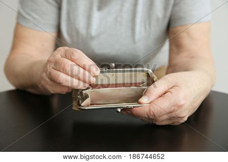 Senior woman with purse sitting at table, closeup. Poverty concept