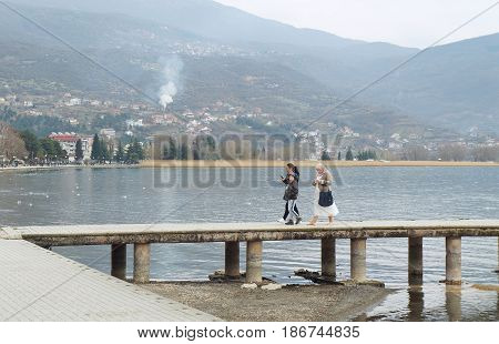 OHRID, MACEDONIA - MARCH 12, 2017: Multicultural family walks on the pier of Ohrid lake