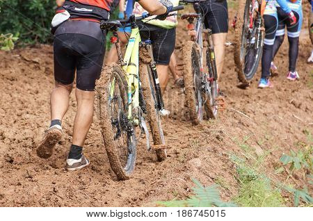 A group of mountain bike cyclists walking through a muddy road / Cycling in wet condition concept