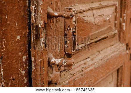 Old door handle painted in brown color closeup