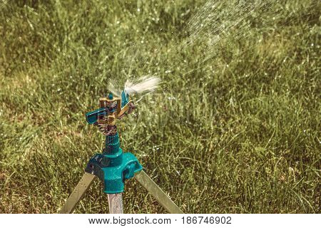 Yard sprinkler on tripod working, copy space
