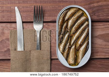Tin can of sprats sardines with knife and fork on wooden table. Top view.