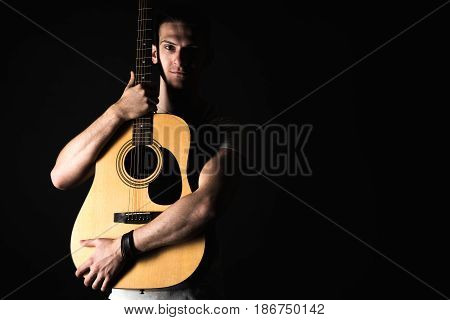 Guitarist, Music. A Young Man Stands With An Acoustic Guitar On A Black Isolated Background. Horizon