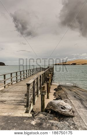 Bay of Islands New Zealand - March 7 2017: Exit to Tasman Sea from Hokianga Harbour shows large dune and pier pointing at entrance all under heavy cloudscape because of approaching cyclone.