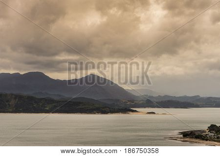 Bay of Islands New Zealand - March 7 2017: Mountains opposite Opononi town on shore of Hokianga Harbour. All under heavy cloudscape because of approaching cyclone.