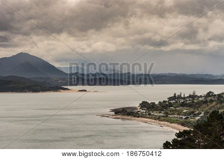 Bay of Islands New Zealand - March 7 2017: Opononi town and mountains on Hokianga Harbour. All under heavy cloudscape because of approaching cyclone.