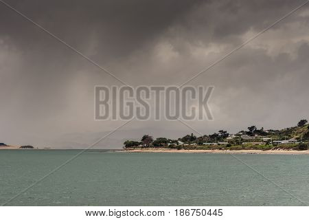 Bay of Islands New Zealand - March 7 2017: Opononi town on shore of Hokianga Harbour. Hokianga River and town under heavy cloudscape because of approaching cyclone.