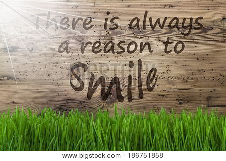 English Quote There Is Always A Reason To Smile. Spring Season Greeting Card. Sunny Aged Wooden Background With Gras.