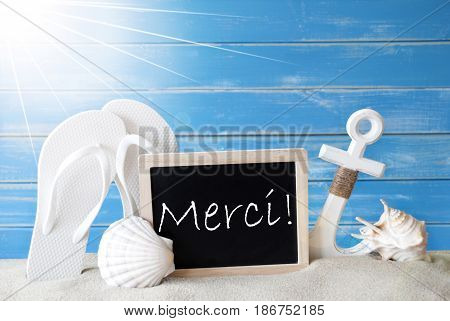 Chalkboard With French Text Merci Means Thank You. Blue Wooden Background. Sunny Summer Card With Holiday Greetings. Beach Vacation Symbolized By Sand, Flip Flops, Anchor And Shell.