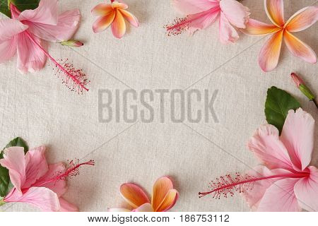 Pink and orange summer flowers on linen copy space background