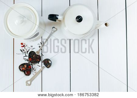 Teatime flat lay. Loose leaf tea , infuser, tea pot and vintage spoons View from above.