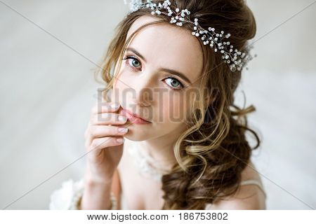 Closeup brunette bride with fashion wedding hairstyle and makeup. Wedding day of bride. Closeup beauty woman. Fashion brunette model indoors. Beauty portrait of model with bridal hairstyle and makeup
