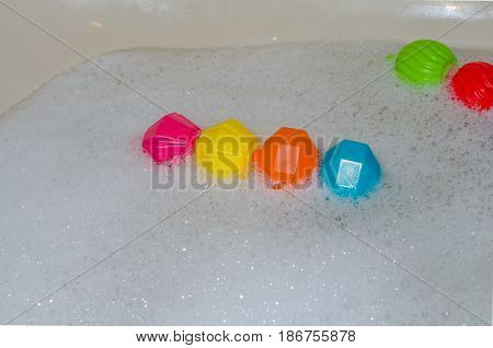 Fun floating children's toys drifting in a bathtub full of bubbles.  Fun and clean bubble bath in the tub.