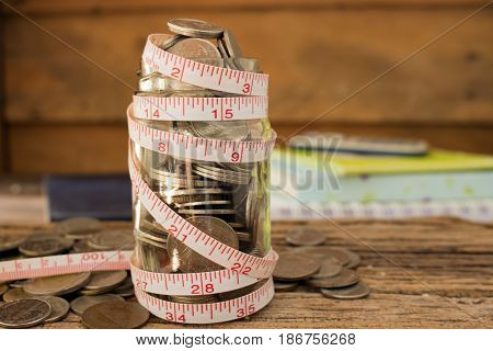 stack of coins and measuring tape for save money concept.