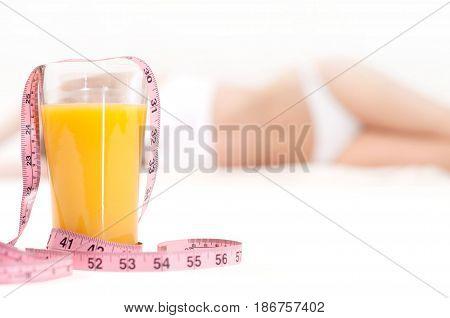 Glass Of Orange Juice And  Measuring Tape