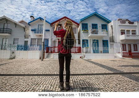 Traveller girl with blonde dreadlocks is takes photo on a smartphone striped houses in Costa Nova, Portugal