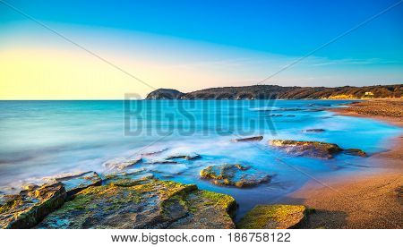 Baratti beach bay travel destination headland hill rocks and sea on sunset. Maremma Tuscany Italy Europe. Long Exposure