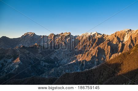 Apuane alpi or Apuan alps snowy mountains and marble quarry at sunset in winter. Carrara Tuscany Italy.