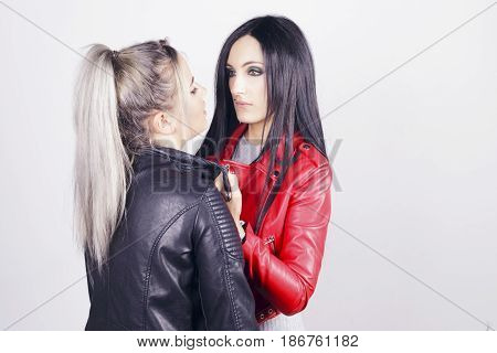 Brunette Woman Pulls A Blonde Woman By The Jacket Flap.