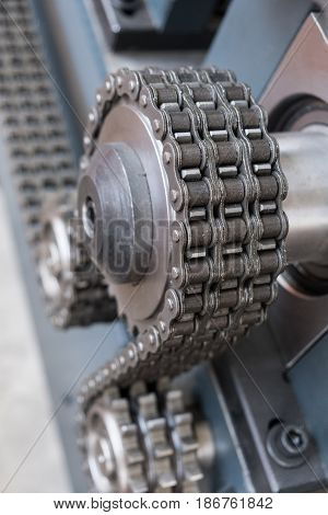Triple strand roller chain going around three sprockets on industrial machine