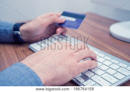 hands holding credit card and a typing on wireless keyboard making online purchase