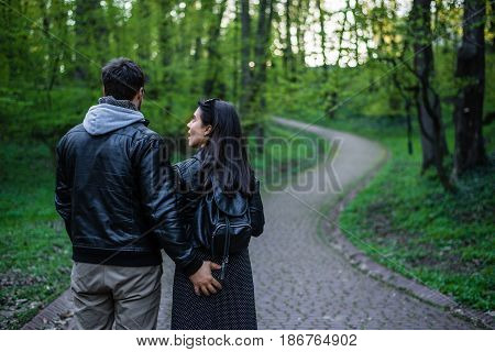 man tocuhs womans ass while walking in city park