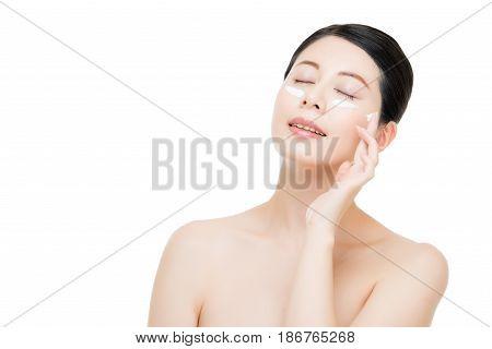 Young Woman Applying Cream Around Eyes