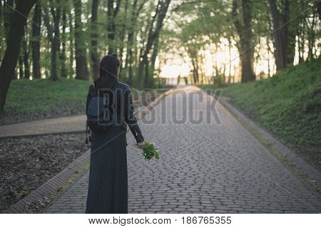 woman walking by city park with flowers in hands