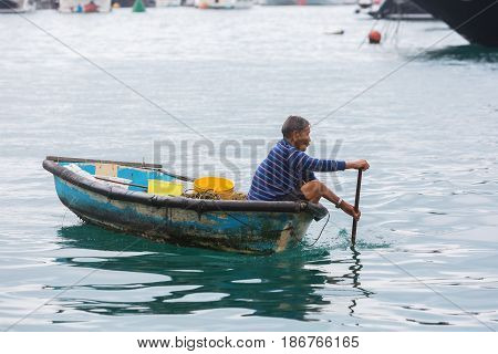 Aberdeen Hong Kong - March 12 2017: unidentified Tanka man in a canoe in the harbour of Aberdeen. Tanka people are boat people an ethnic subgroup in Southern China living on boats in the harbour