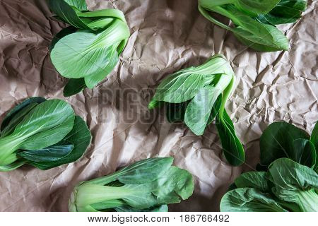 close up Fresh baby green bok choy on crumpled paper overhead or top view shot