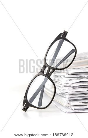 the reading eyeglasses with stacking of newspaper background business information concept