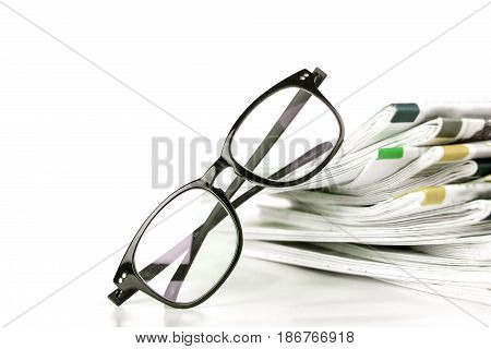 selective focus on reading eyeglasses with stacking of the newspaper background business information concept