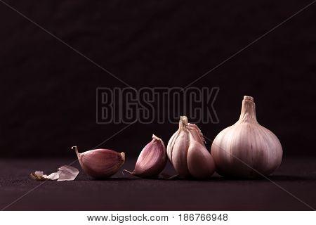 still life arrangement of Three whole garlic bulbs grouped on black stone plate