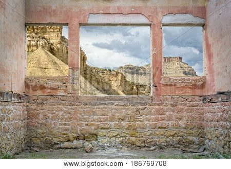 Book Cliffs in eastern Utah as seen through windows of a ruin ghost town building