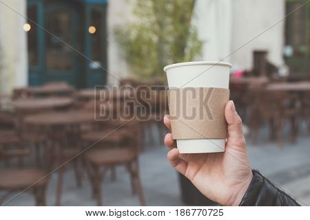 cup of coffee in hand with caffe on background