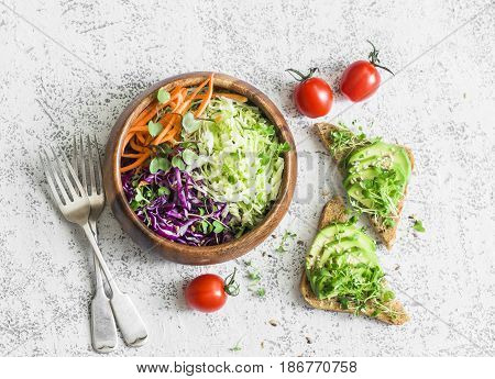 Spring healthy vegetarian snack - cabbage salad and sandwiches with avocado and micro greens on a light table top view.