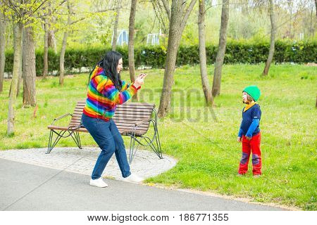 Mother making photos with her phone to his son in the park