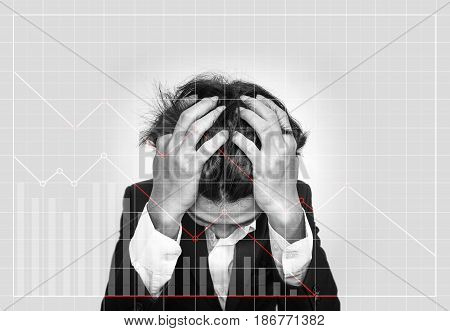 Stressed out businessman, with downward business graphs. Failure stock market and loss business investment profit concepts