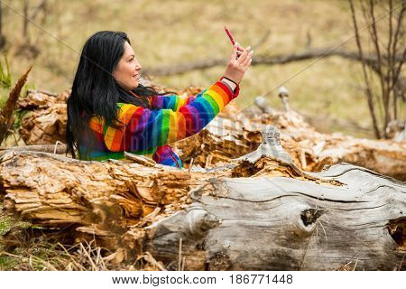 Happy woman in middle of some bark trees making selfie