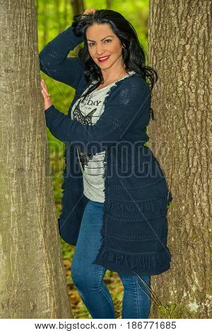 Woman posing in the forest between trees