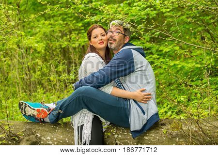 Cheerful couple sitting on a tree in forest
