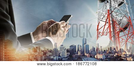 Businessman using smartphone with double exposure modern city in sunrise, and telecommunication towers